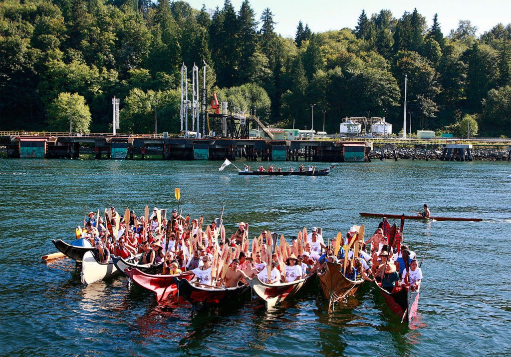 Paddlers from Squamish, Tsleil-Waututh, and other Coastal First Nations perform a water ceremony in front of the Kinder Morgan's Westridge Marine Terminal. (CNW Group/Tsleil-Waututh Nation)